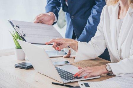 Photo pour Crochet vue d'un homme d'affaires tenant un presse-papiers près d'une femme d'affaires utilisant un ordinateur portatif sur le lieu de travail - image libre de droit