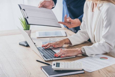 Photo pour Vue partielle d'un homme d'affaires tenant un presse-papiers près d'une femme d'affaires utilisant un ordinateur portable sur le lieu de travail - image libre de droit