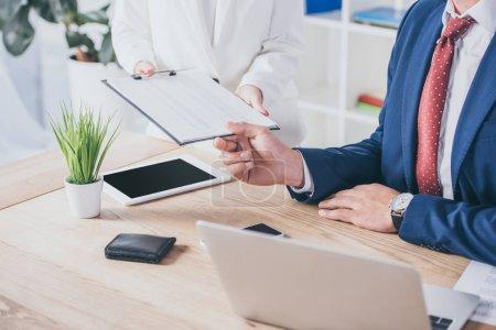 Photo pour Crochet vu d'une femme d'affaires tenant un porte-papiers près d'un homme d'affaires assis sur son lieu de travail - image libre de droit