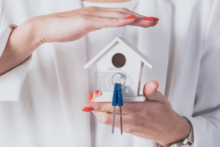 cropped view of businesswoman holding and covering house model and keys with hand