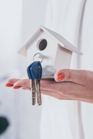 Photo for Partial view of businesswoman holding house model with keys - Royalty Free Image