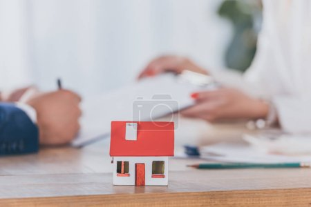 Photo for Selective focus of house model near businesswoman holding clipboard and client signing contract - Royalty Free Image