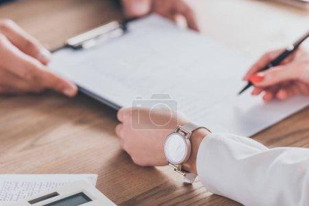 Photo pour Vue recadrée de la femme dans le contrat de signature de montre-bracelet près du concessionnaire - image libre de droit