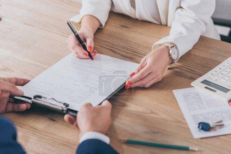 Photo pour Crochet vue d'un homme d'affaires tenant un presse-papiers et d'une femme signant un contrat - image libre de droit