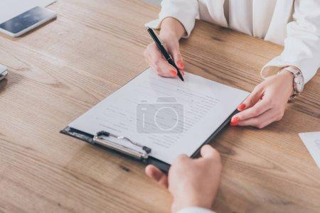 Photo pour Vue partielle d'un homme d'affaires détenant un presse-papiers et d'une femme signant un contrat - image libre de droit