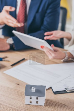 Photo for Selective focus of house model near woman holding digital tablet and businessman pointing with hand - Royalty Free Image