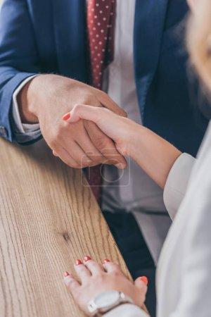 Photo pour Voir un homme d'affaires serrer la main d'une femme assise sur un bureau de bois - image libre de droit