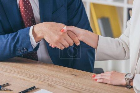 Photo pour Vue partielle d'un homme d'affaires serrant la main d'une femme assise sur un bureau de bois - image libre de droit