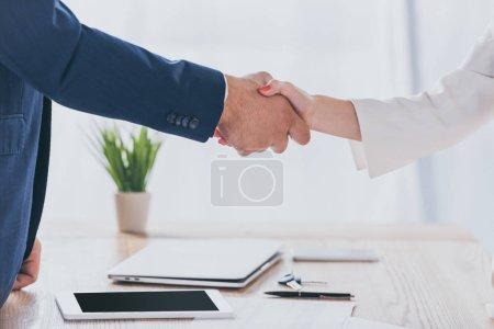 Foto de Vista parcial del hombre de negocios estrechando la mano con la mujer mientras está sentado en el escritorio de madera - Imagen libre de derechos