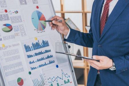 Photo pour Crochet vue d'un homme d'affaires en tenue officielle analyse de l'infographie sur le tableau à feuilles - image libre de droit
