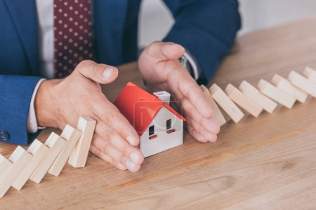 Photo for Cropped view of risk manager protecting house model from domino effect of falling wooden blocks with hands - Royalty Free Image