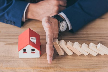 Photo pour Vue en coupe du gestionnaire des risques protégeant le modèle de maison contre la chute de blocs de bois à la main - image libre de droit
