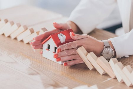 Photo for Cropped view of risk manager protecting house model from falling wooden blocks with hands - Royalty Free Image