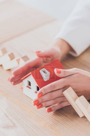 Photo for Partial view of businesswoman protecting house model from falling wooden blocks with hands - Royalty Free Image