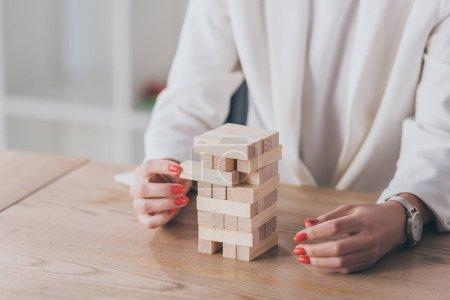 Photo pour Crochet vue d'une femme d'affaires sortant un bloc de bois de la pile - image libre de droit