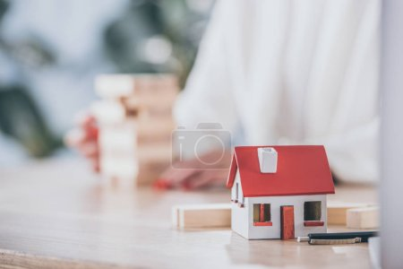 Photo for Selective focus of house model near risk manager and wooden blocks - Royalty Free Image