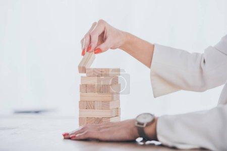 Photo pour Crochet vue d'une femme d'affaires mettant un bloc de bois sur une pile - image libre de droit