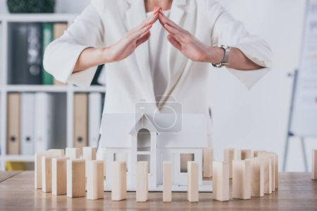 Photo for Partial view of risk manager covering house model surrounded with wooden blocks with hands - Royalty Free Image