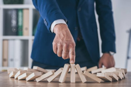 Photo for Cropped view of risk manager stopping domino effect of falling wooden blocks - Royalty Free Image