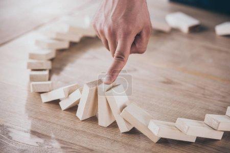Photo pour Crochet vue d'un homme d'affaires arrêtant l'effet domino de la chute de blocs de bois - image libre de droit