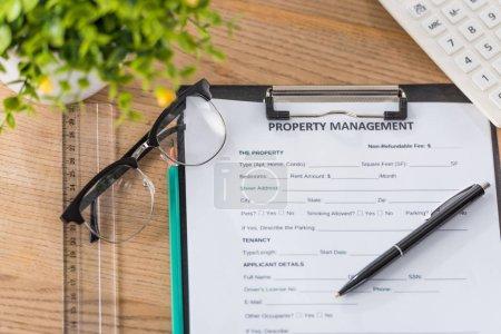 Photo pour Vue du haut de la planche à papiers avec entente de gestion immobilière, stylo, lunettes, calculatrice et plante verte sur un bureau en bois - image libre de droit