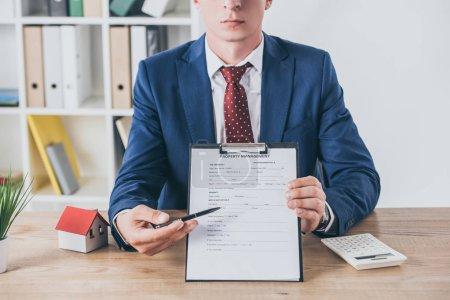Photo pour Crochet vue d'un homme d'affaires tenant une planche à papiers avec entente de gestion immobilière près de la maison modèle et calculatrice - image libre de droit