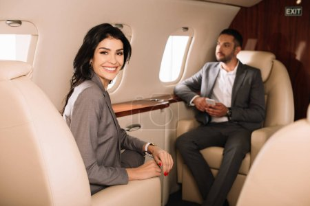 Photo for Selective focus of cheerful businesswoman in private jet with businessman - Royalty Free Image