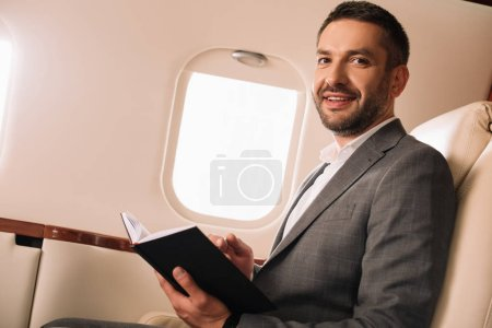 cheerful businessman holding notebook in private jet