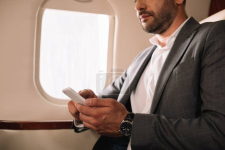 Photo for Cropped view of bearded businessman using smartphone in private jet - Royalty Free Image