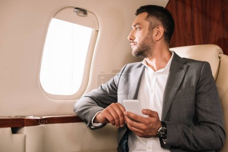 Photo for Handsome businessman looking at airplane window while using smartphone in private jet - Royalty Free Image