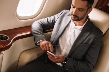 Photo pour Bel homme d'affaires barbu utilisant un smartphone en jet privé - image libre de droit
