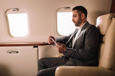 Photo pour Vue latérale d'un bel homme d'affaires en costume utilisant un téléphone intelligent dans un jet privé - image libre de droit