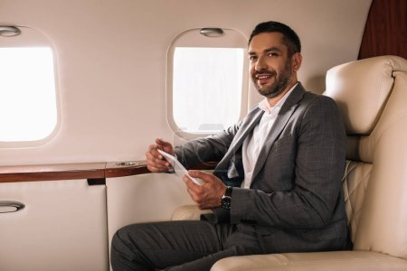 cheerful bearded businessman in suit using smartphone in private jet