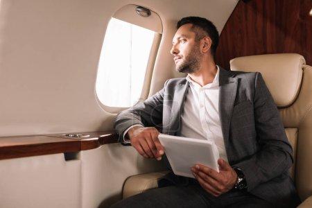 Photo pour Homme d'affaires barbu en costume tenant tablette numérique tout en regardant la fenêtre de l'avion en jet privé - image libre de droit