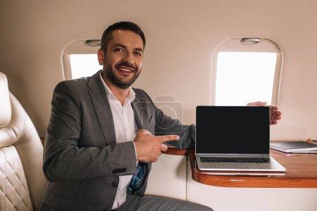 Photo pour Homme d'affaires heureux pointant avec le doigt à l'ordinateur portable avec écran blanc dans le jet privé - image libre de droit