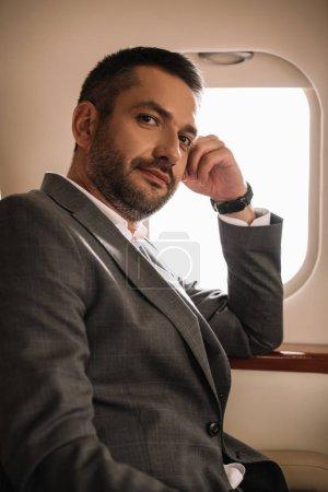 Photo pour Bel homme d'affaires assis près de la fenêtre de l'avion en jet privé - image libre de droit