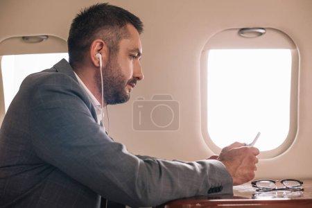 Photo pour Vue latérale de l'homme d'affaires dans les écouteurs en utilisant smartphone en jet privé - image libre de droit
