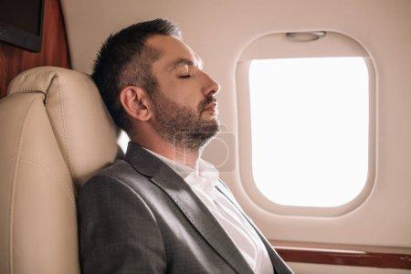 Photo pour Vue latérale de l'homme d'affaires barbu avec les yeux fermés assis en jet privé - image libre de droit