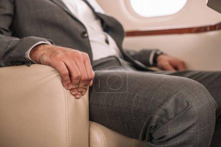 Photo pour Crochet vu d'un homme d'affaires assis dans un jet privé - image libre de droit