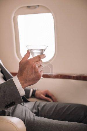 Photo pour Vue recadrée de l'homme d'affaires tenant verre de martini avec boisson en jet privé - image libre de droit