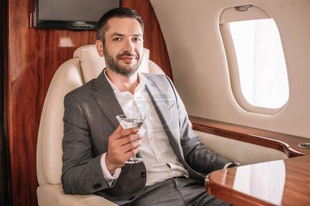 Photo pour Foyer sélectif de l'homme d'affaires heureux tenant verre de martini avec boisson en jet privé - image libre de droit