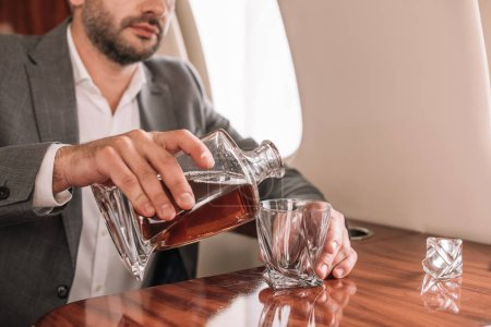 Photo for Cropped view of bearded businessman pouring whiskey in glass in plane - Royalty Free Image
