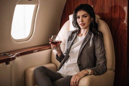 Photo pour Femme d'affaires tenant du verre avec du cognac dans un jet privé - image libre de droit