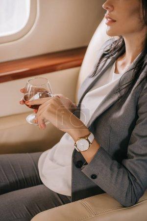 Photo pour Vue recadrée de femme d'affaires en tenue formelle tenant verre avec cognac en jet privé - image libre de droit