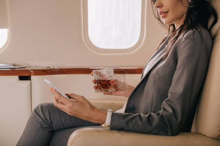 Photo for Cropped view of businesswoman in formal wear holding glass with whiskey and smartphone in private jet - Royalty Free Image