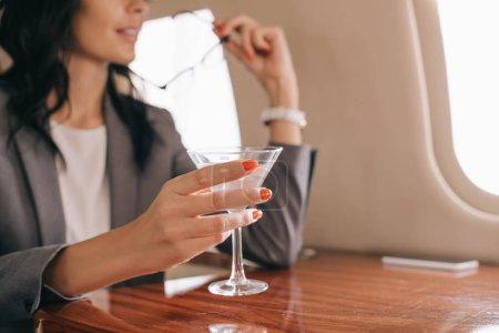 Photo pour Vue recadrée de femme d'affaires tenant du verre de martini en jet privé - image libre de droit