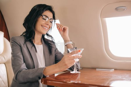 Photo for Cheerful businesswoman in eye glasses holding martini glass in private jet - Royalty Free Image