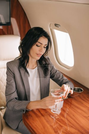 Photo for Beautiful businesswoman holding martini glass in private jet - Royalty Free Image