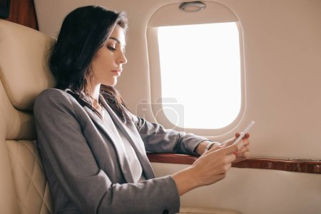 Photo for Side view of businesswoman using smartphone in private jet - Royalty Free Image