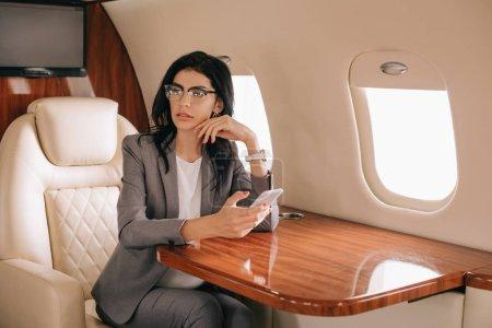 Photo pour Femme d'affaires en lunettes utilisant un téléphone intelligent dans un jet privé - image libre de droit